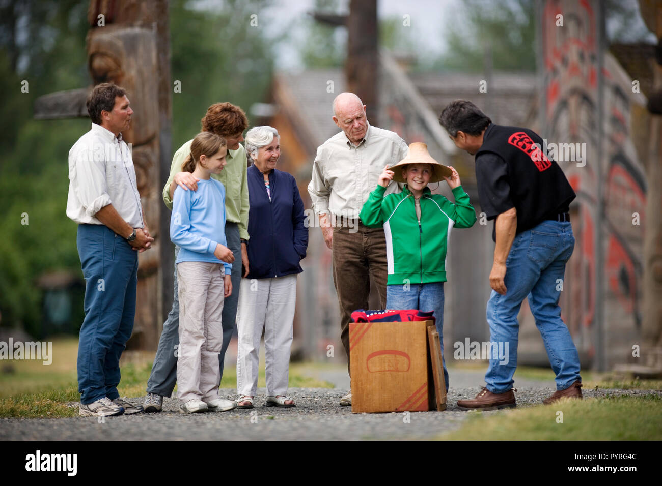 Young boy trying on a hat while standing next to his family. - Stock Image
