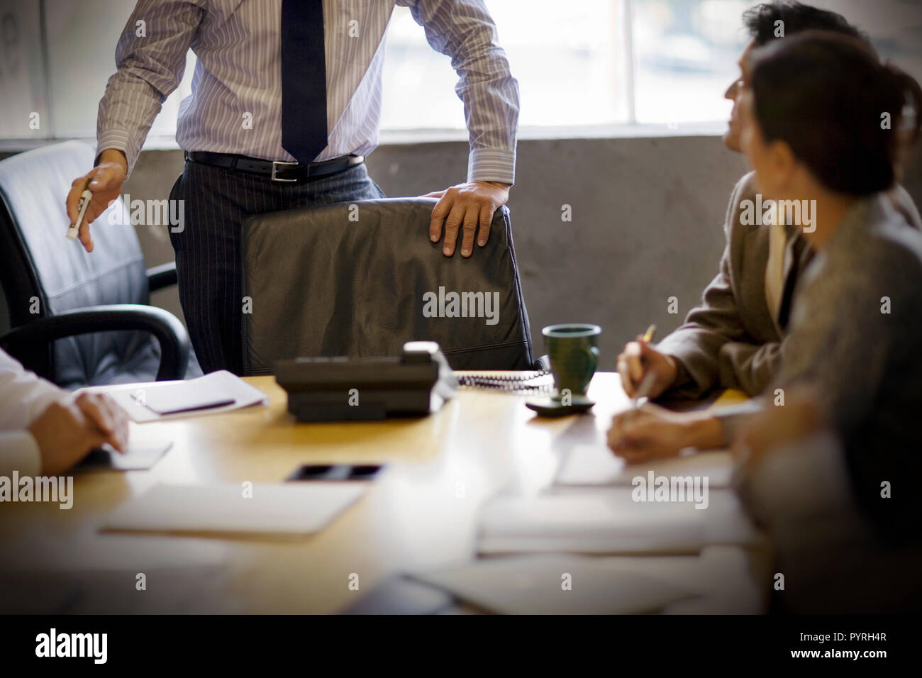 Group of business people sitting in a boardroom. - Stock Image