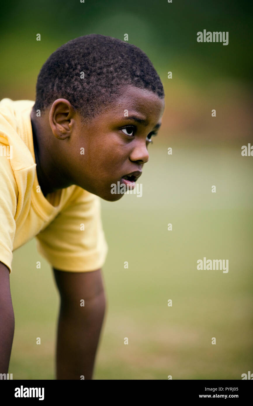 Determined young boy crouching down in preparation for a race. - Stock Image