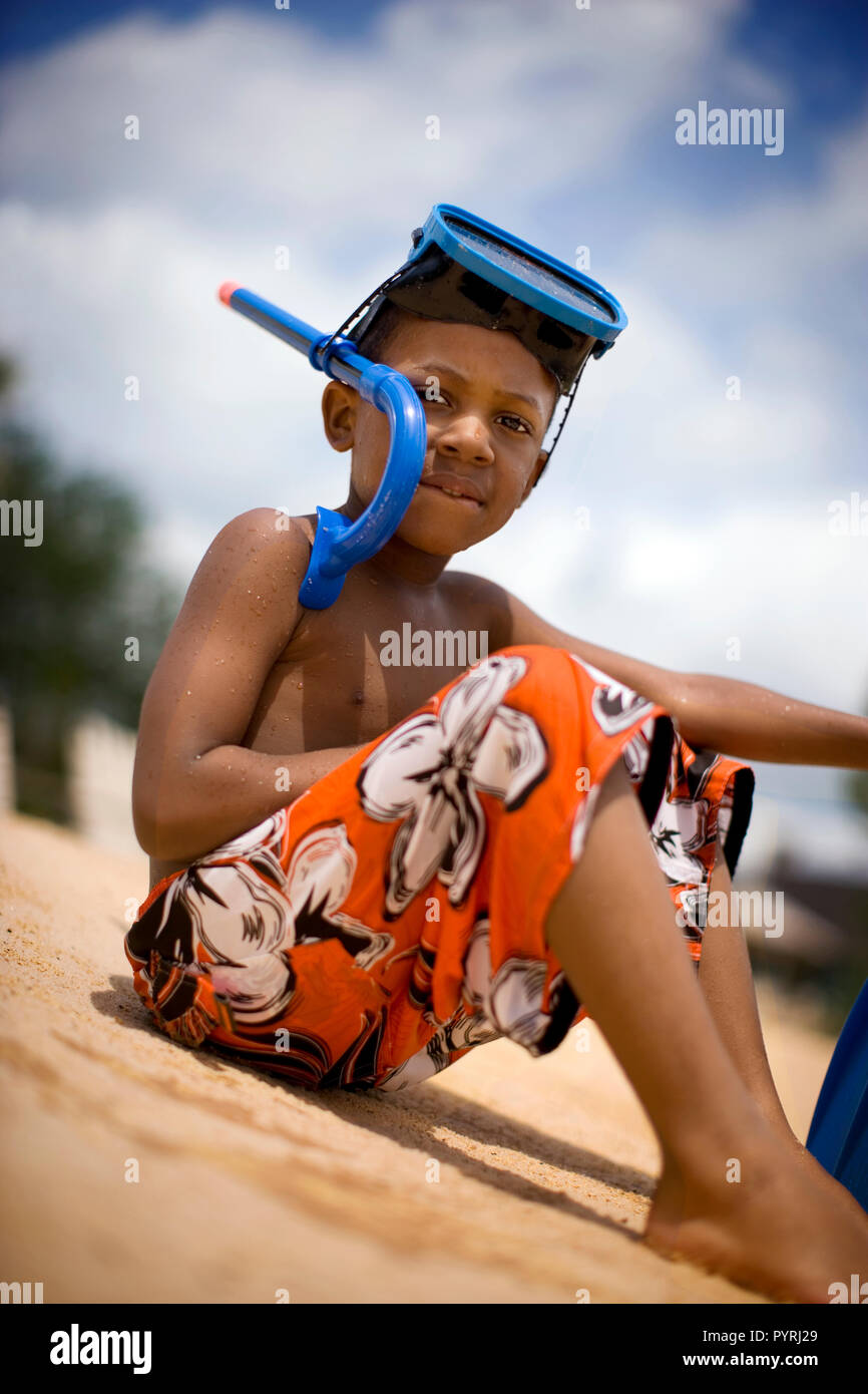 Portrait of a young boy wearing a swimming mask and snorkel while sitting on the beach. - Stock Image