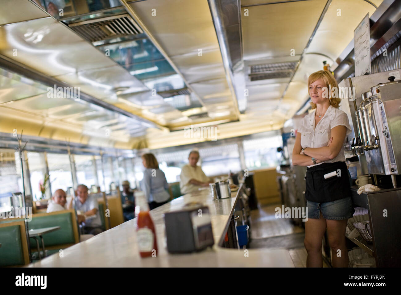 Waitress standing behind counter in old fashioned diner Stock Photo