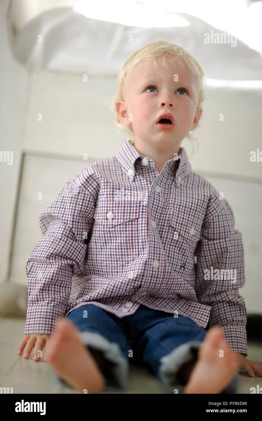 Young boy sitting on the floor with his mouth open. - Stock Image