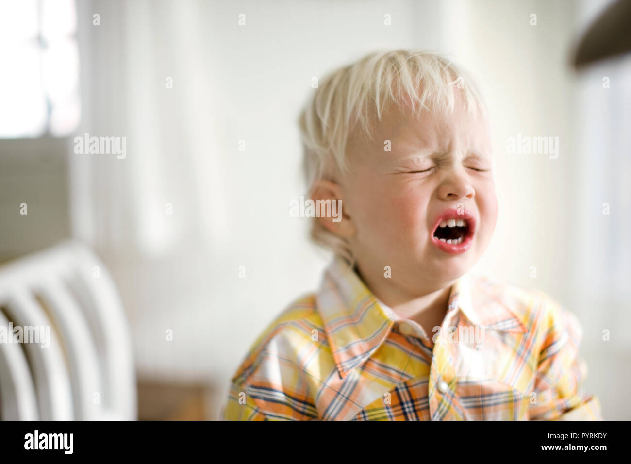 Upset toddler screwing his face up. - Stock Image