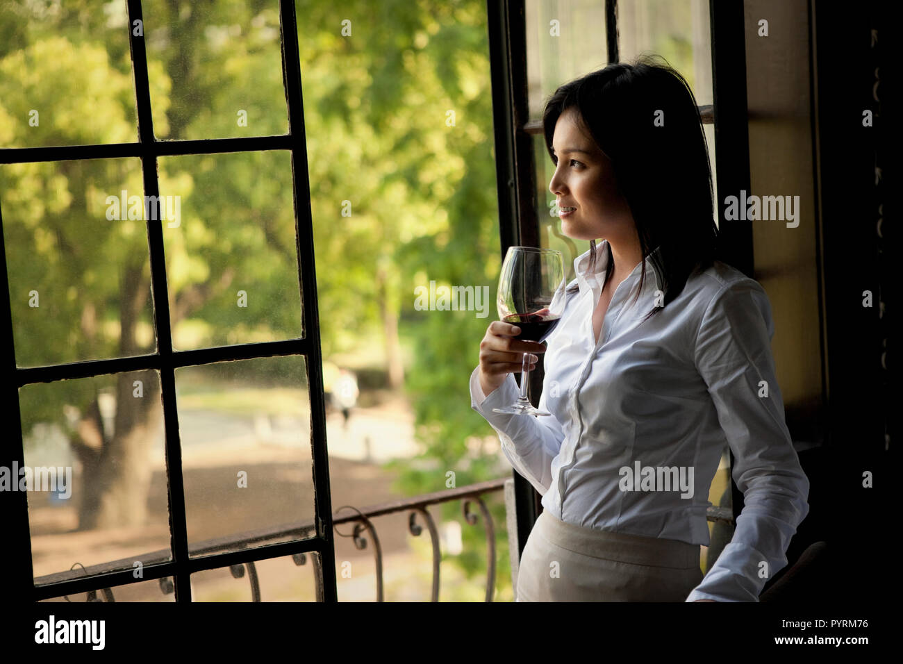 Mid-adult woman holding a glass of red wine while looking out a window.. - Stock Image