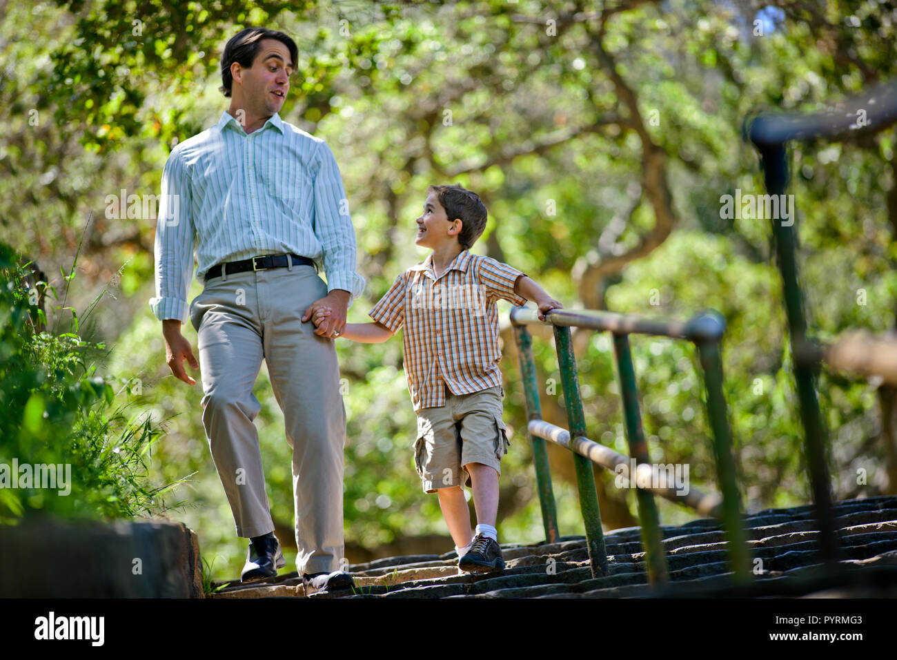 Happy father and son walking down stairs in a park. Stock Photo