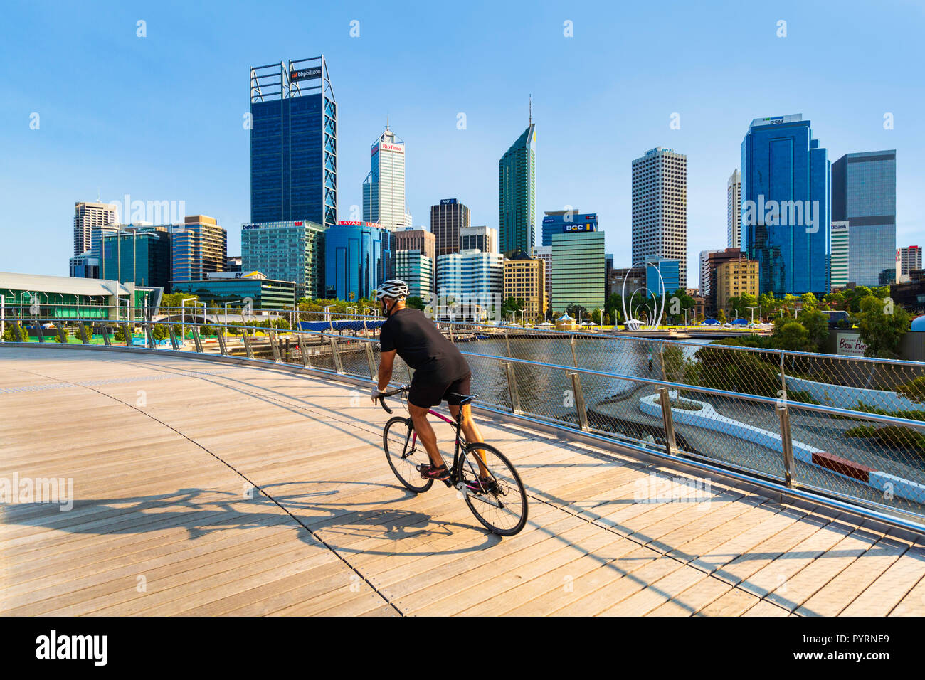 A man cycling over Elizabeth Quay Bridge with a view of Perth city in the background. Elizabeth Quay - Stock Image
