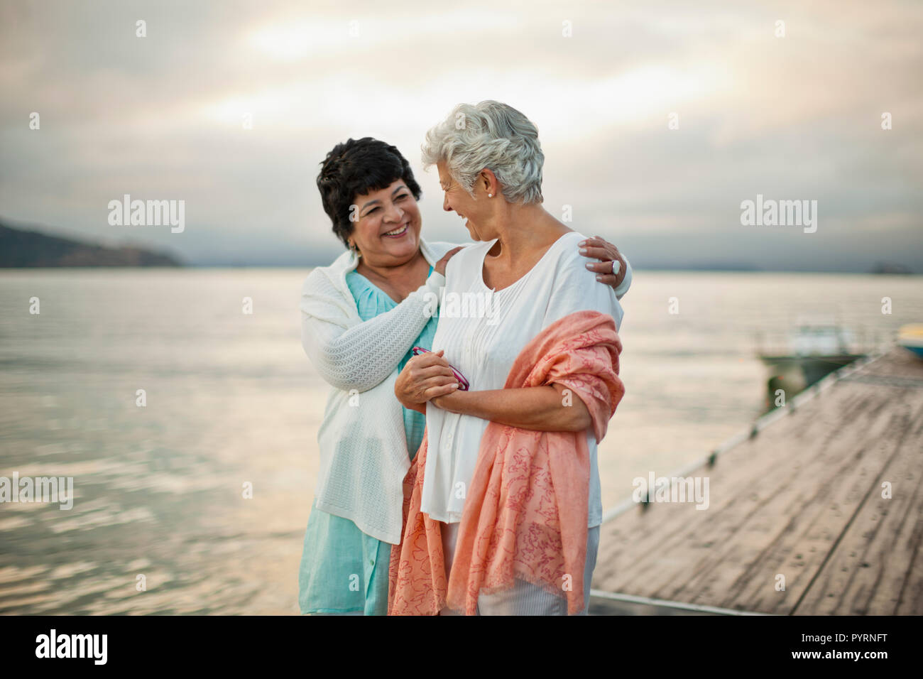 Two happy mature women have fun together as they chat and walk along a jetty. - Stock Image