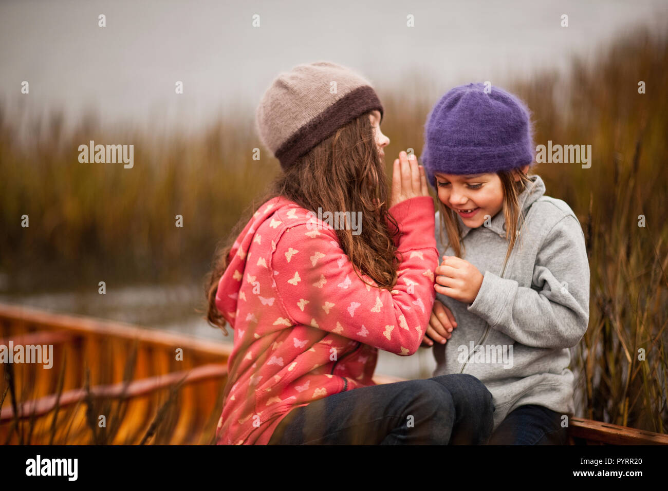 Two sisters tell secrets and laugh as they sit together in a wooden canoe among reeds reeds on a lakeshore. - Stock Image
