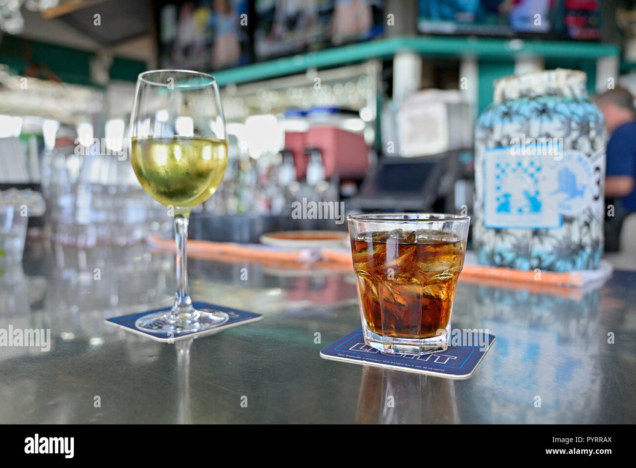 Mixed drink possibly a Bourbon and Coke or Rum and Coke along with a glass of white wine on the bar at Bud and Alley's, Seaside Florida USA. Stock Photo
