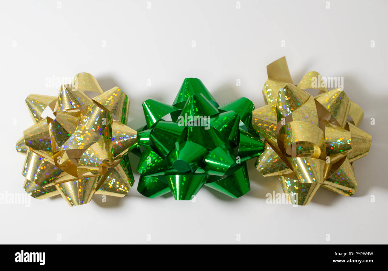Christmas Holiday Gift Wrapping Bows 2 gold and 1 green. Light White Background. Plenty of room for copy. Brilliant colors. - Stock Image