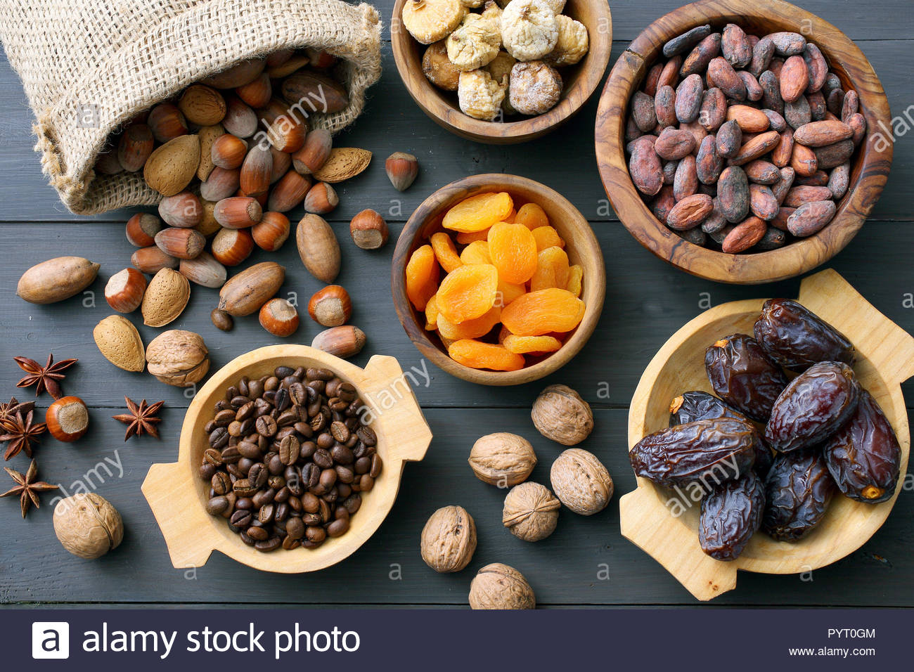 Different dried fruits and nuts in wooden bowls Stock Photo