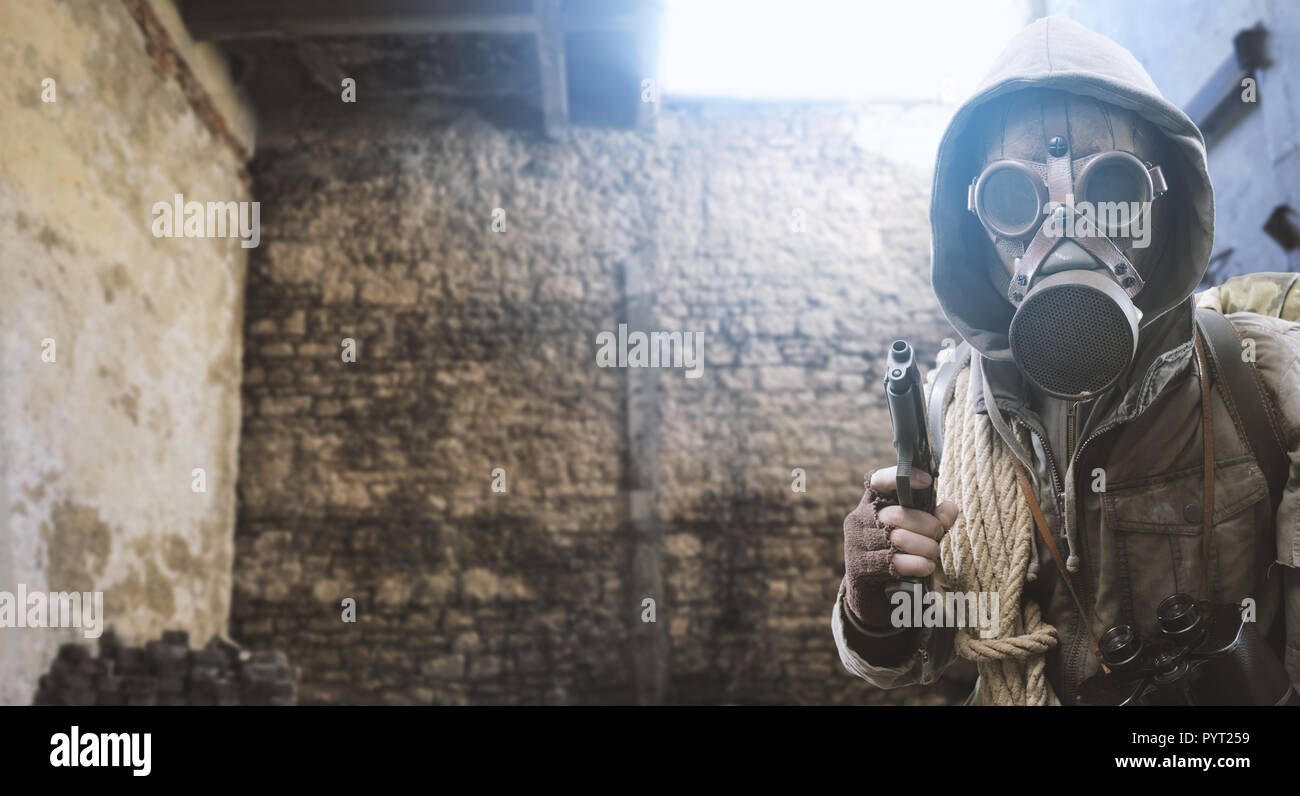 Post atomic survivor in a post apocalyptic setting, he is wearing a gas mask and pointing a gun: environmental disaster and chemical warfare concept - Stock Image