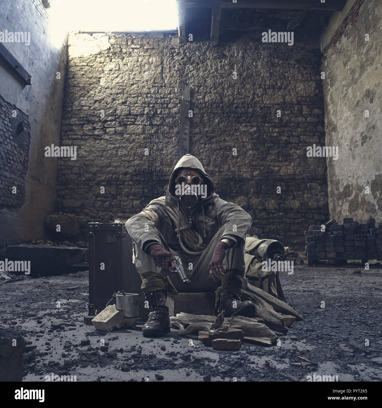 Nuclear disaster survivor in a post apocalyptic setting, he is wearing a gas mask and holding a gun: environmental disaster and chemical warfare conce - Stock Image