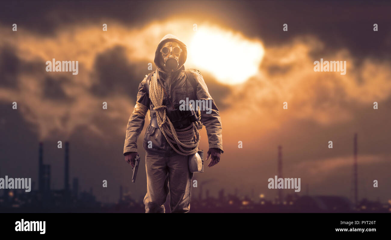 Brave post apocalyptic survivor with gas mask and a gun; polluting industries, toxic smog hiding the sun and environmental degradation in the backgrou - Stock Image
