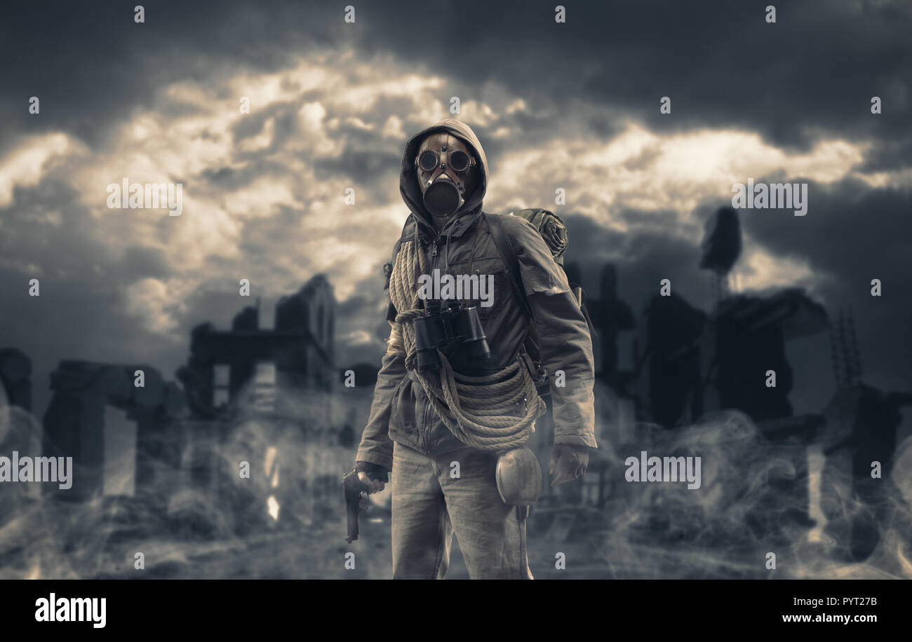 Post apocalyptic survivor standing with a gas mask and a gun, destroyed city and toxic smog in the background: environmental disaster and armageddon c - Stock Image