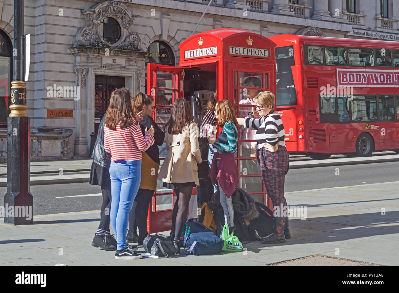 A party of young female tourists deciding to test the capacity of a traditional red telephone box in London's Waterloo Place. - Stock Image
