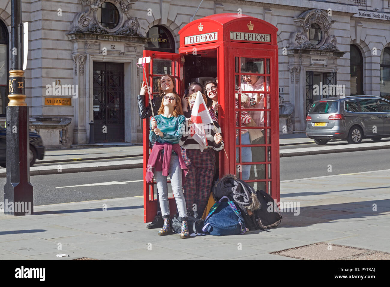 A party of young female tourists taking a selfie after testing the capacity of a traditional red telephone box in London's Waterloo Place. - Stock Image
