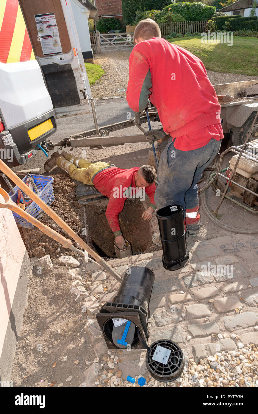Installing a new water meter in the road. UK. Man leaning into a hole to make the installation - Stock Image