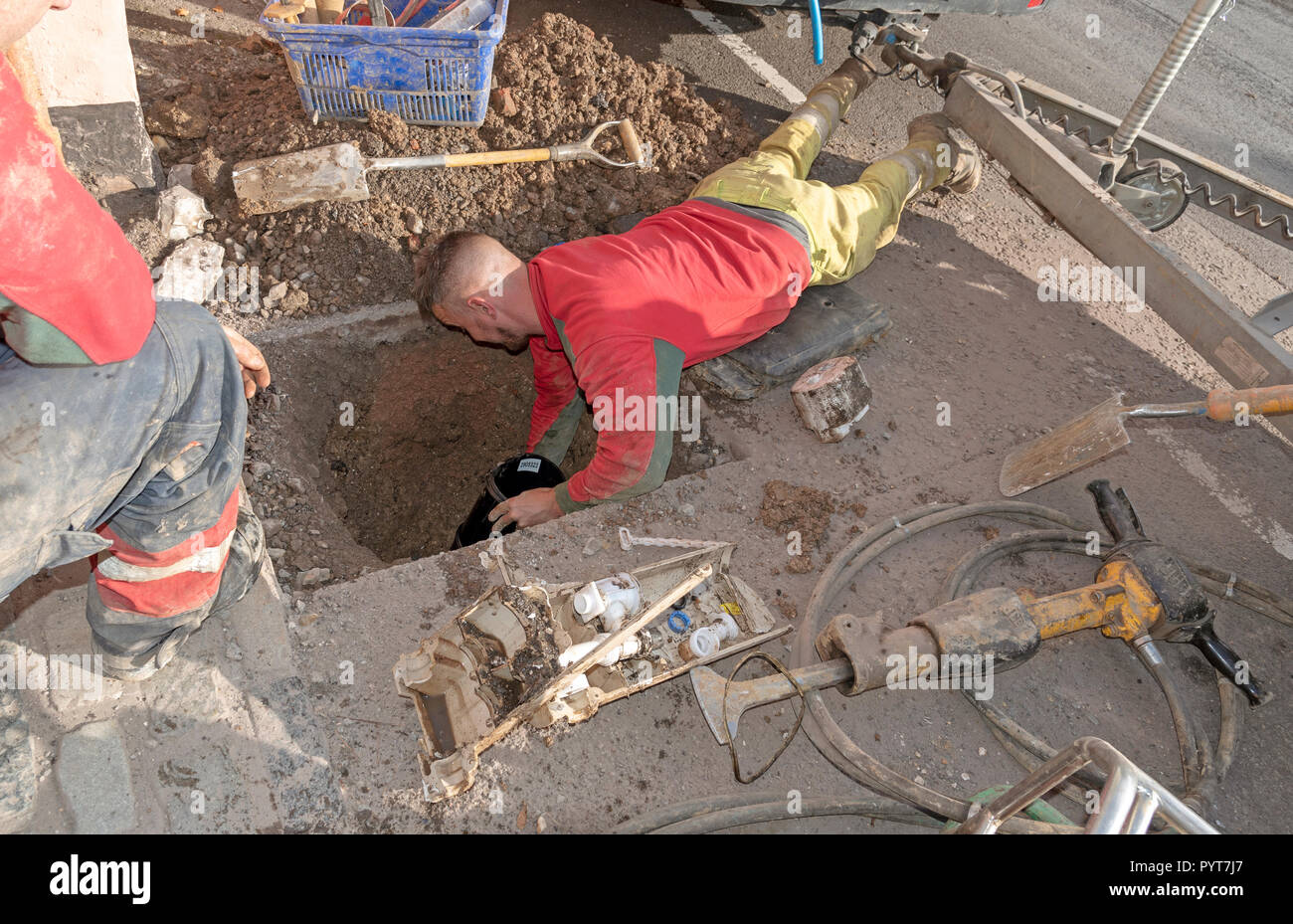 Installing a new water meter in the road. UK. Worker working face down installs the new black plastic meter housing. - Stock Image