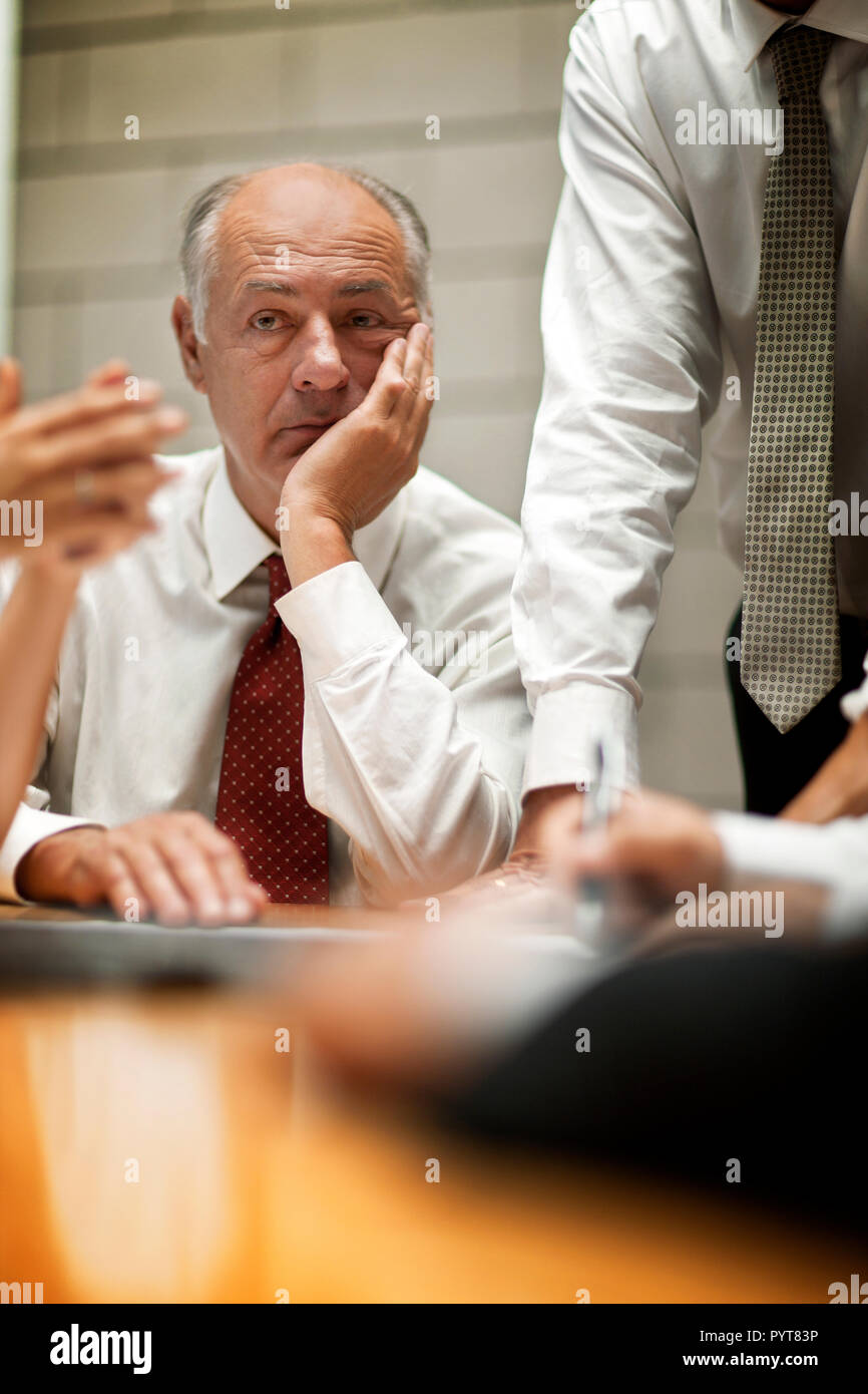 Bored, unhappy businessman rests his chin on a hand and daydreams while his colleagues conduct a business meeting. - Stock Image