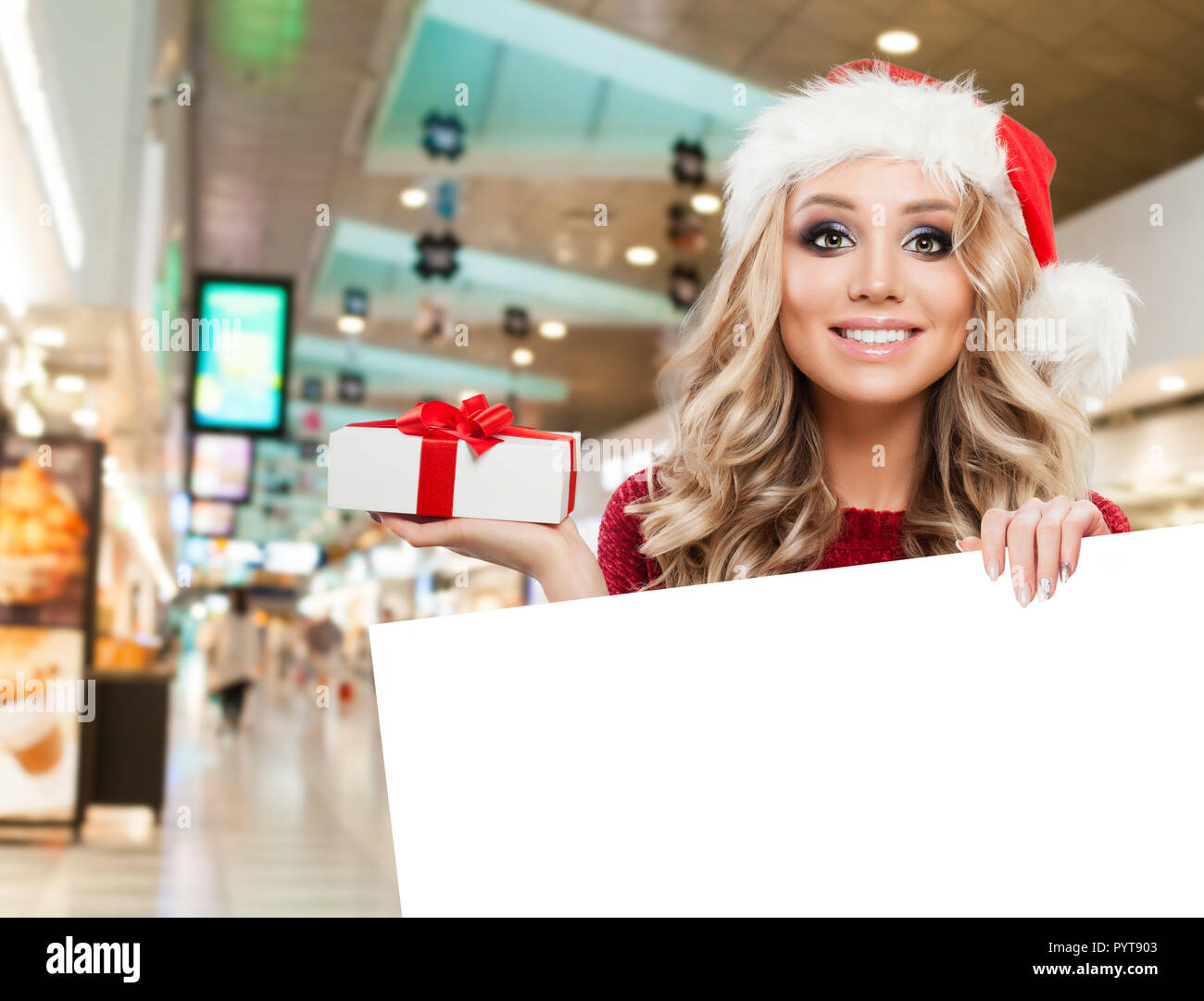 e372162869655 Happy woman Santa showing gift and white empty paper signboard banner with  copy space on shopping mall background. Christmas and New Year sale and off