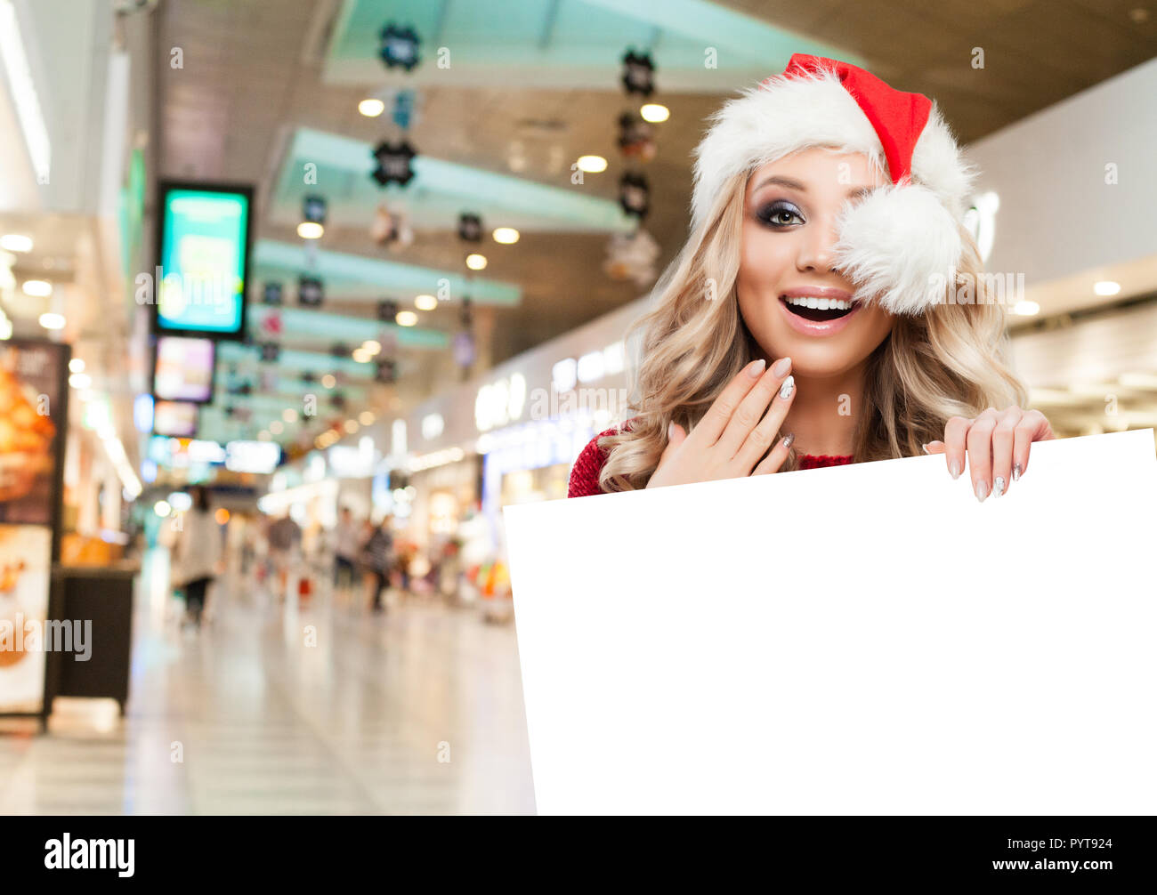 surprised woman in santa hat showing big white empty paper signboard banner with copy space on shopping mall background christmas and new year sale a