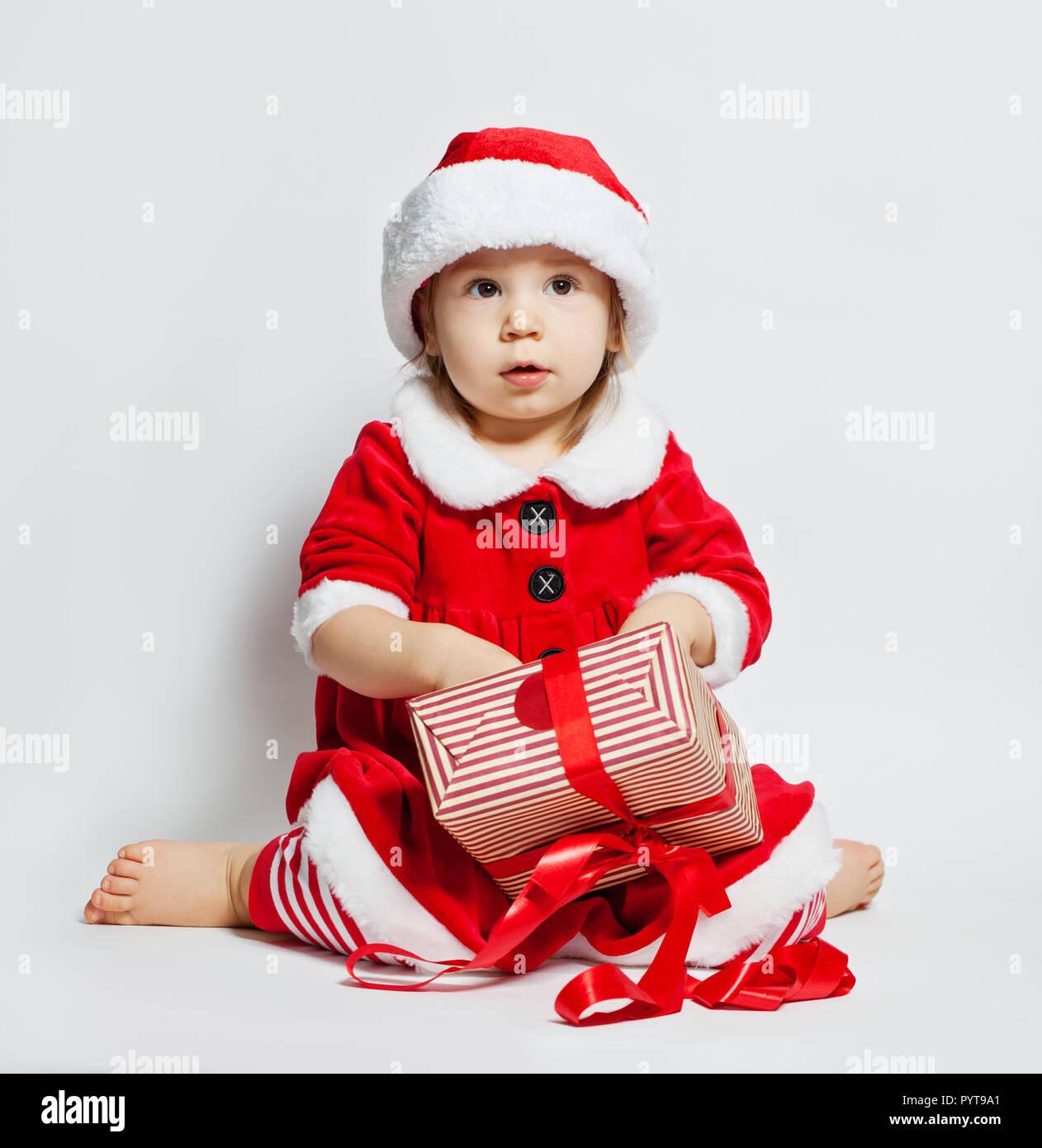 7c5b66b6392 Christmas child in Santa hat opening Xmas gift box on white background