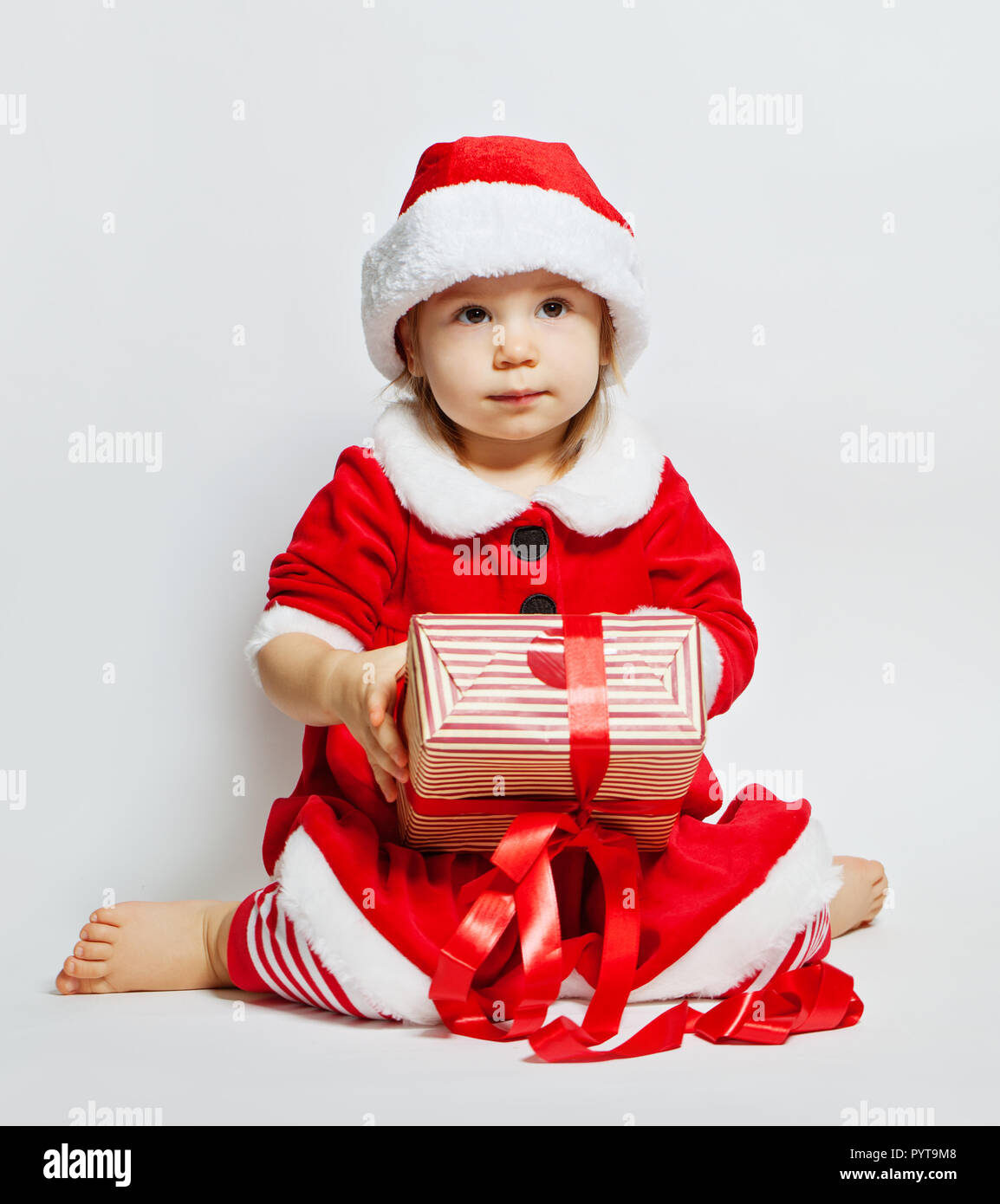 f2c78ddf7 Cute baby in santa hat with Christmas gift box on white background - Stock  Image
