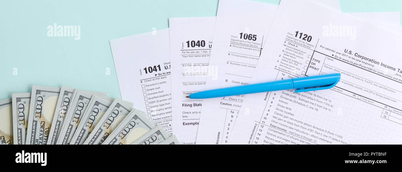 Tax forms lies near hundred dollar bills and blue pen on a light