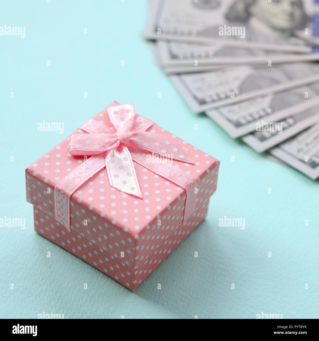 pink dotted gift box lies near hundred dollar bills on a light blue