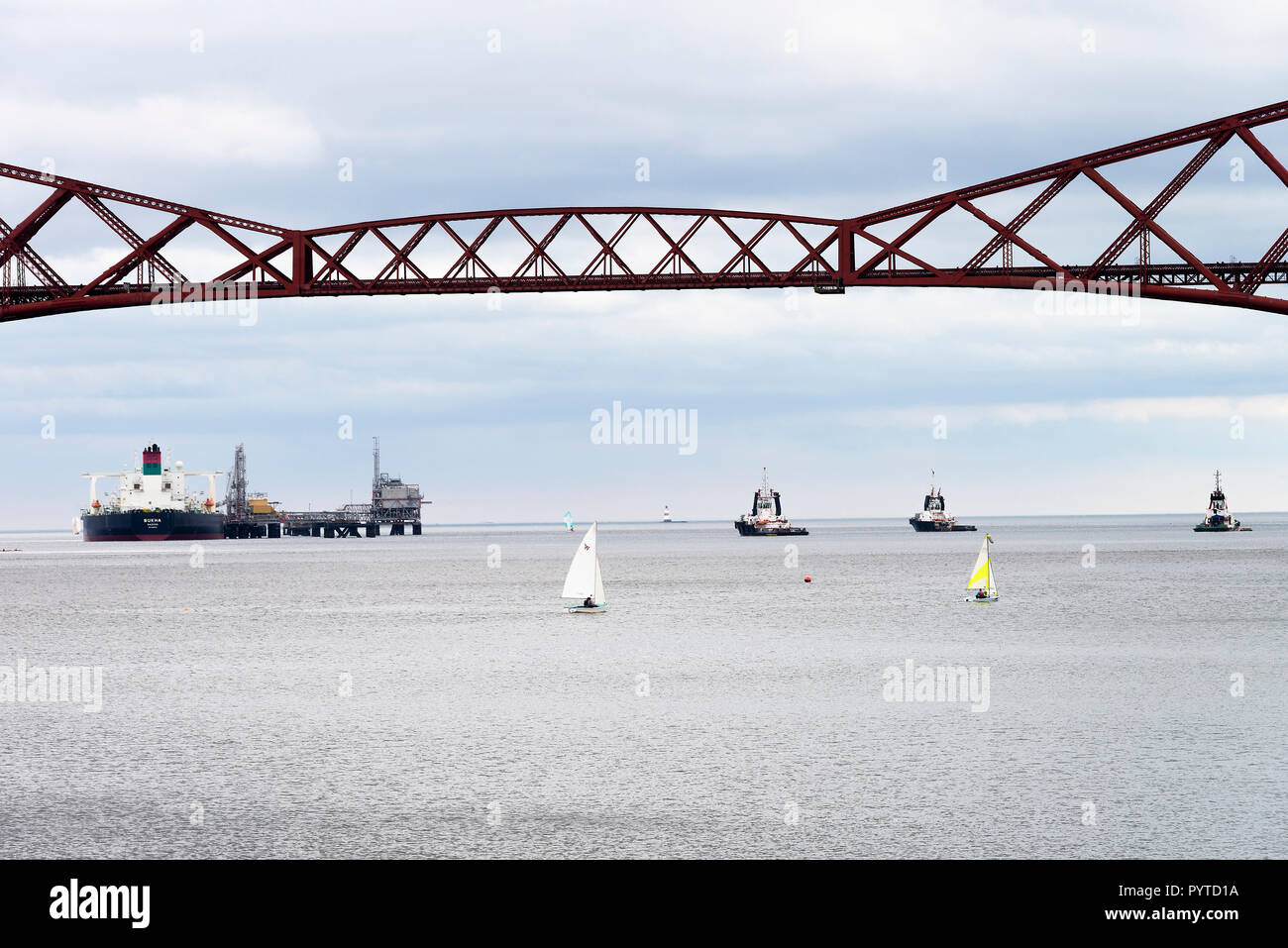 The Forth Rail Bridge Crossing the Firth of Forth with a the Crude Oil Tanker Bukha Discharging Oil at South Queensferry Edinburgh Scotland UK - Stock Image