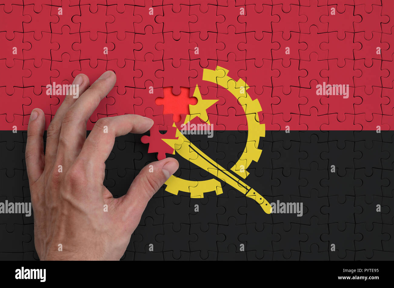 Angola flag  is depicted on a puzzle, which the man's hand completes to fold. - Stock Image