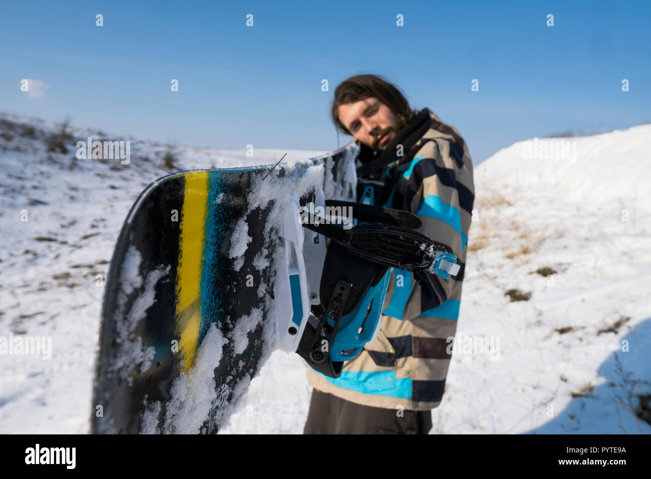 Snowboarder with a long hair holding a snowboard like a gun. Extreme winter sport. - Stock Image