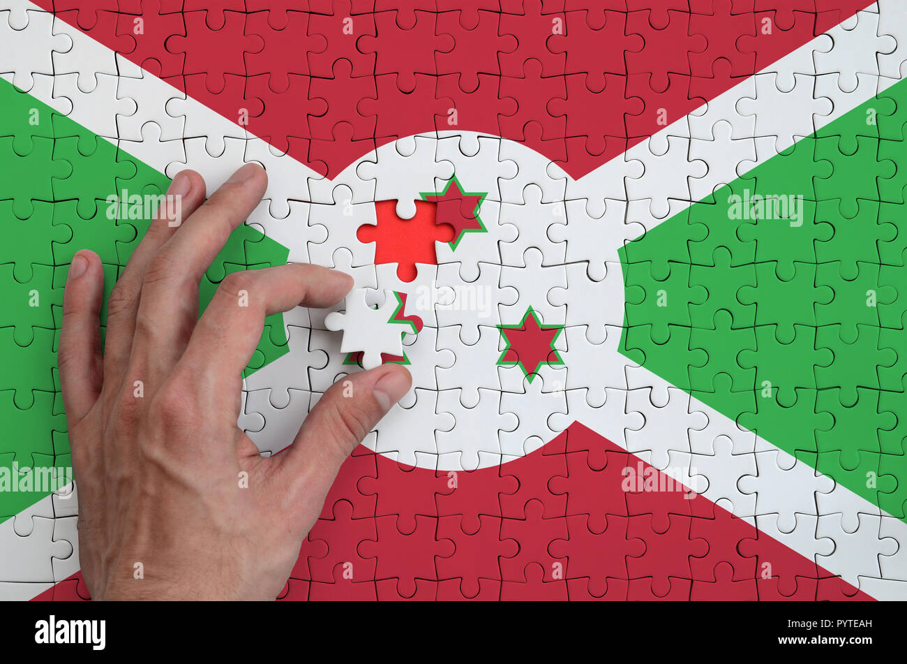 Burundi flag  is depicted on a puzzle, which the man's hand completes to fold. - Stock Image