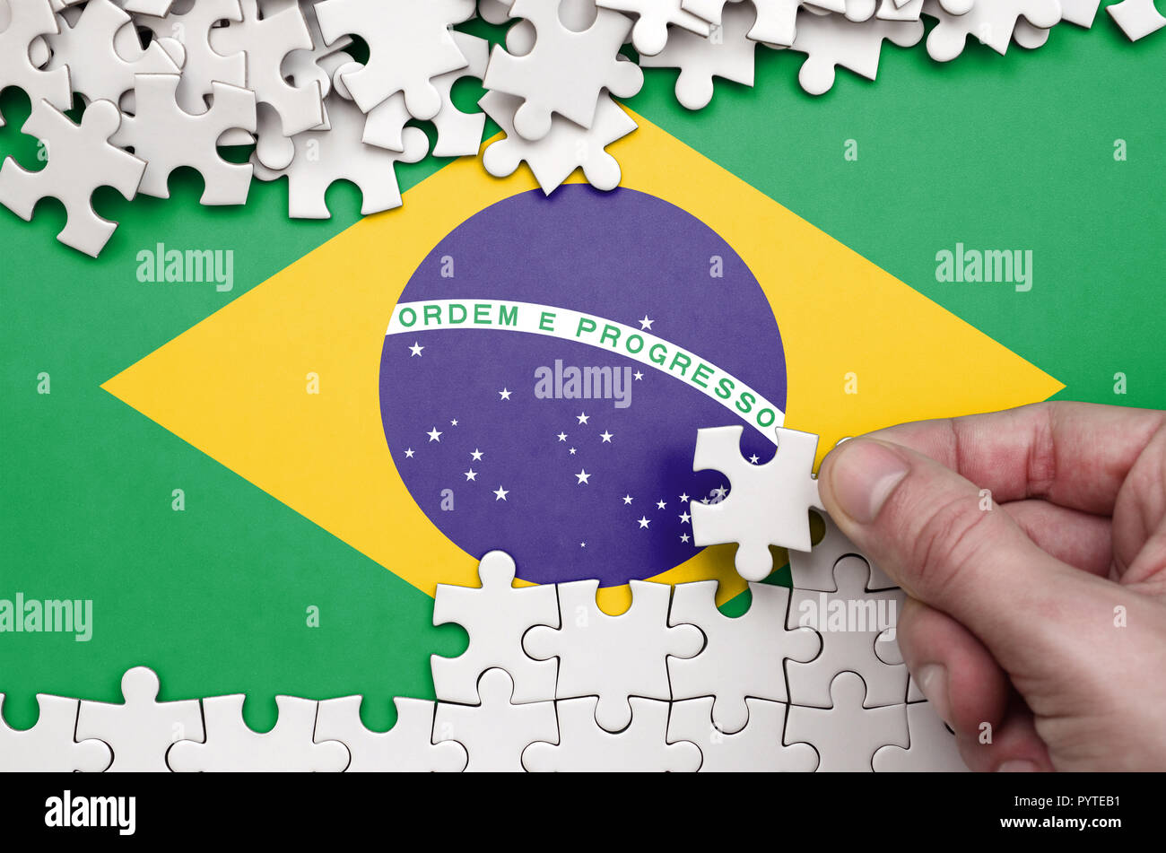 Brazil flag  is depicted on a table on which the human hand folds a puzzle of white color. - Stock Image
