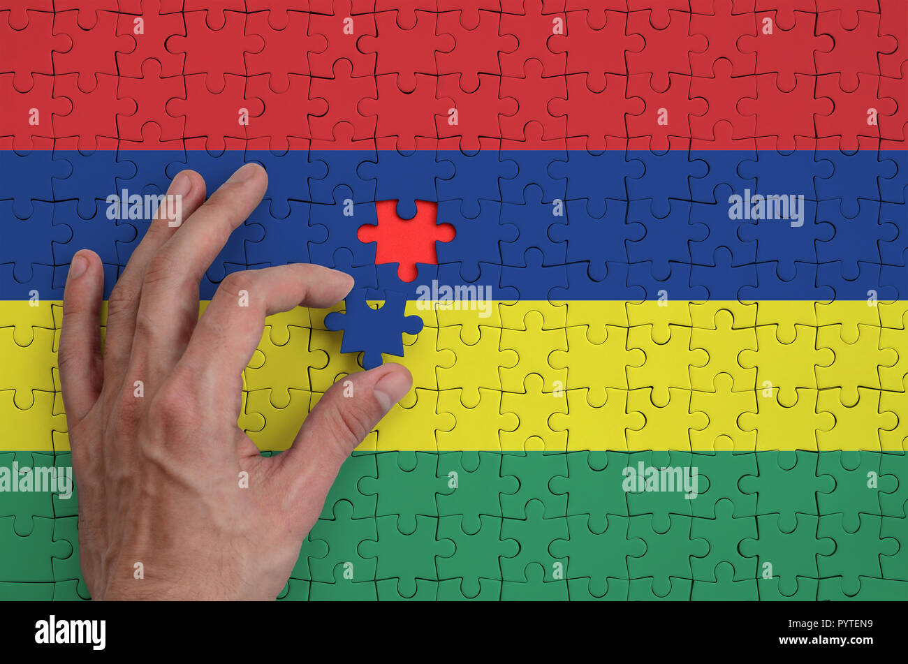 Mauritius flag  is depicted on a puzzle, which the man's hand completes to fold. - Stock Image