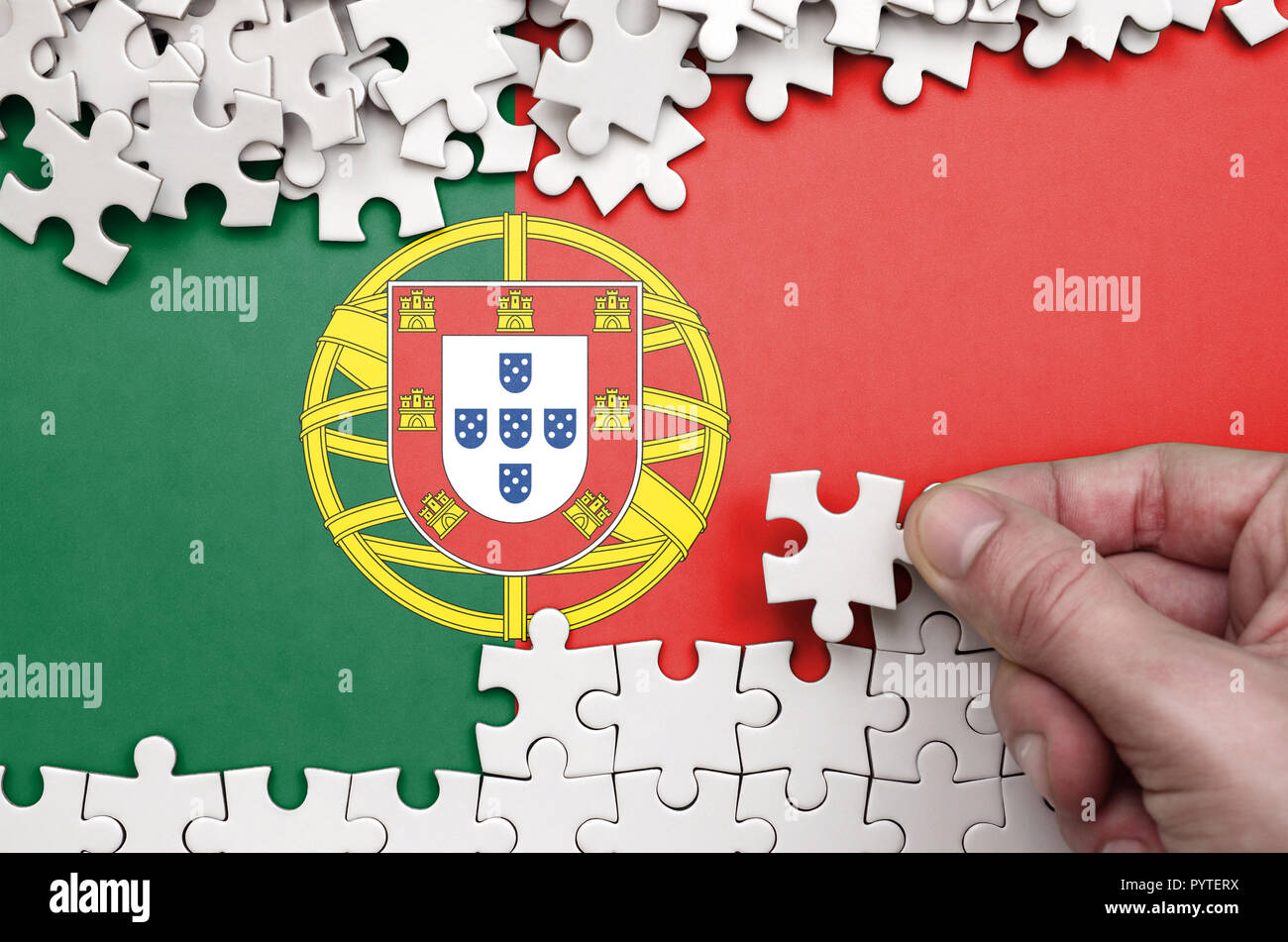 Portugal flag  is depicted on a table on which the human hand folds a puzzle of white color. - Stock Image