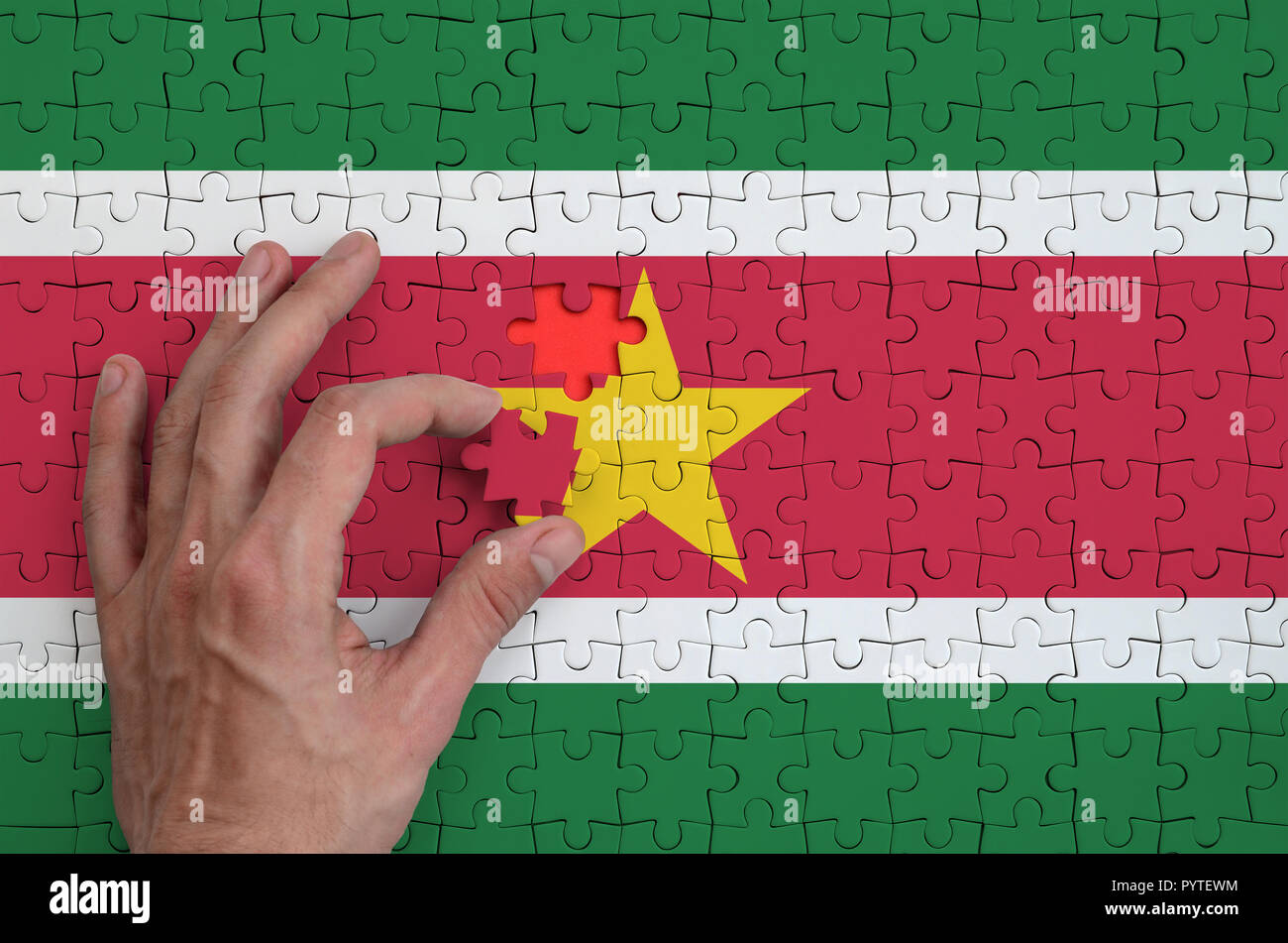 Suriname flag  is depicted on a puzzle, which the man's hand completes to fold. - Stock Image