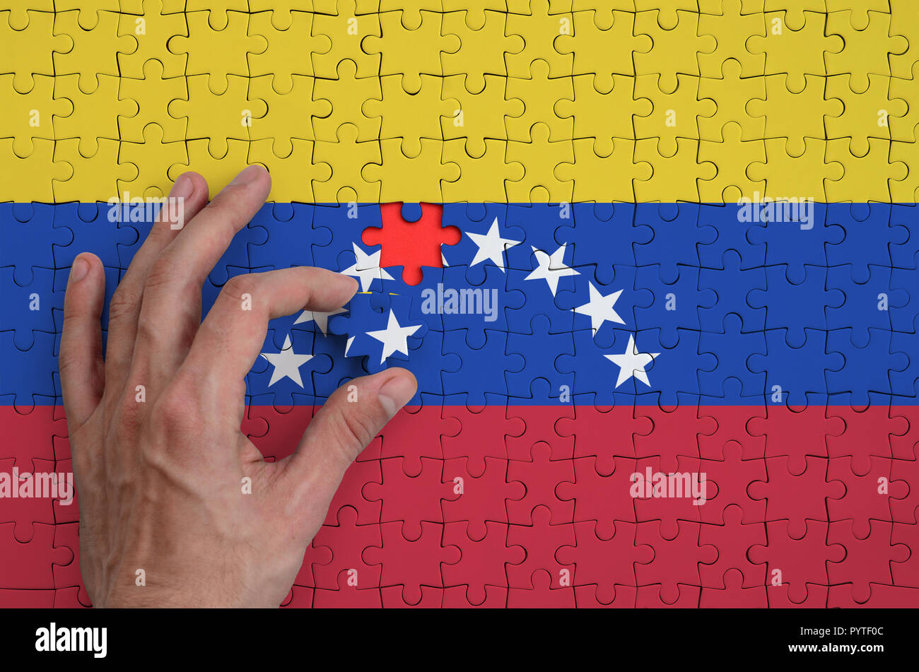 Venezuela flag  is depicted on a puzzle, which the man's hand completes to fold. - Stock Image