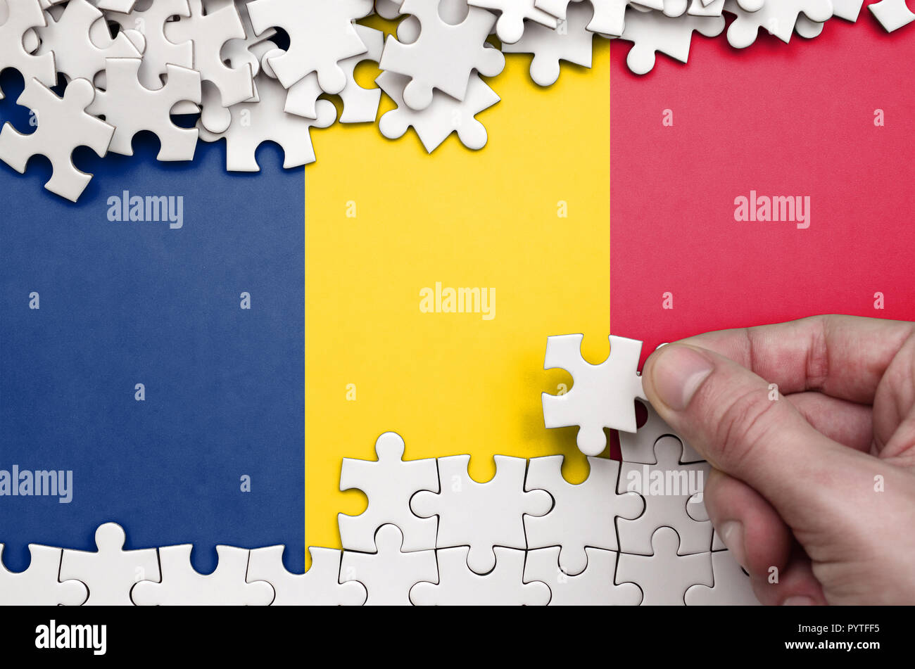 Chad flag  is depicted on a table on which the human hand folds a puzzle of white color. - Stock Image