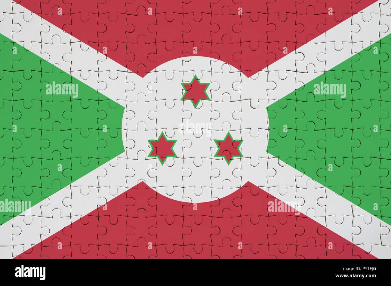 Burundi flag  is depicted on a folded puzzle - Stock Image