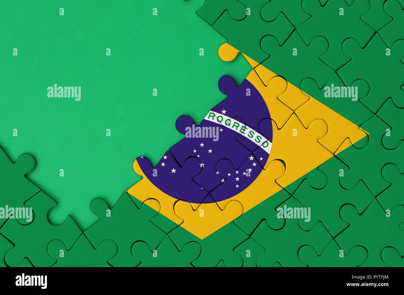 Brazil flag  is depicted on a completed jigsaw puzzle with free green copy space on the left side. - Stock Image