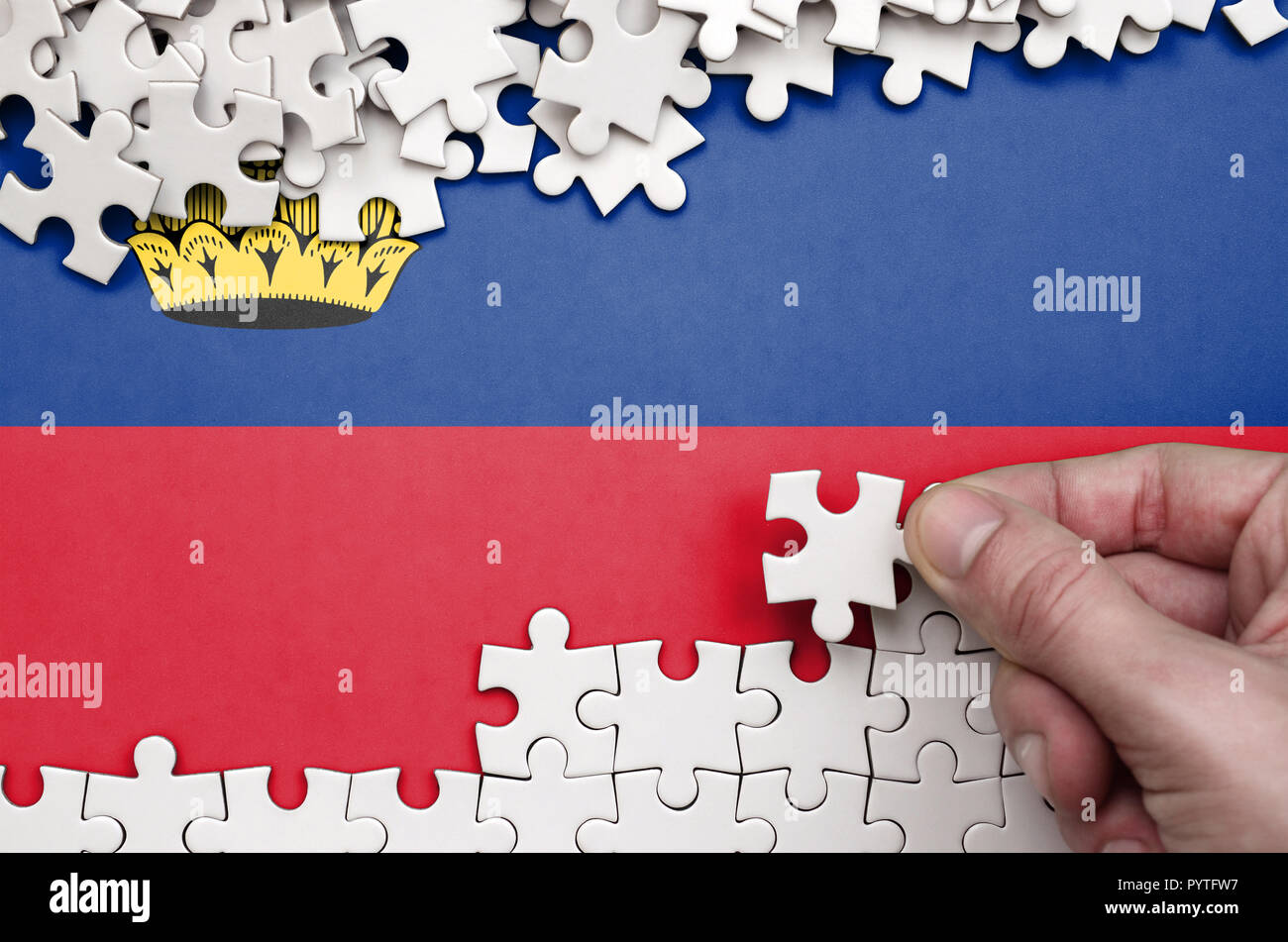 Liechtenstein flag  is depicted on a table on which the human hand folds a puzzle of white color. Stock Photo
