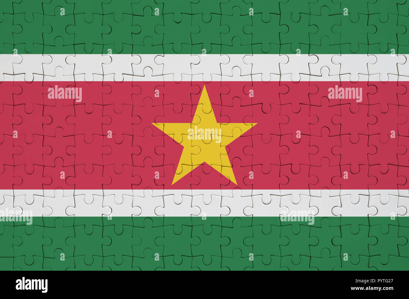 Suriname flag  is depicted on a folded puzzle - Stock Image