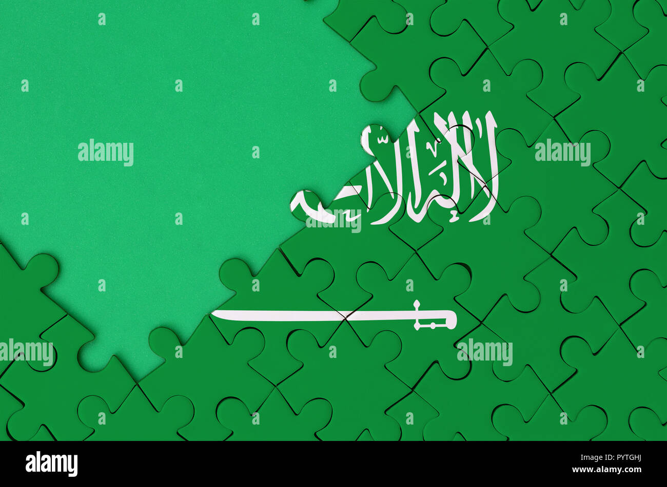 Saudi Arabia flag  is depicted on a completed jigsaw puzzle with free green copy space on the left side. - Stock Image