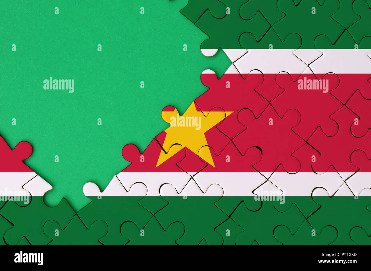 Suriname flag  is depicted on a completed jigsaw puzzle with free green copy space on the left side. - Stock Image