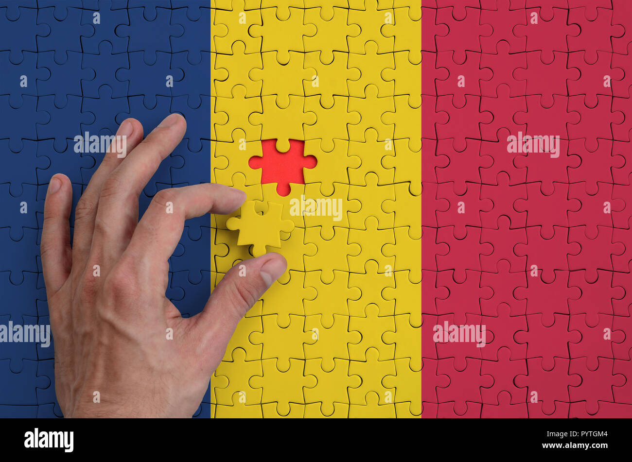 Chad flag  is depicted on a puzzle, which the man's hand completes to fold. - Stock Image