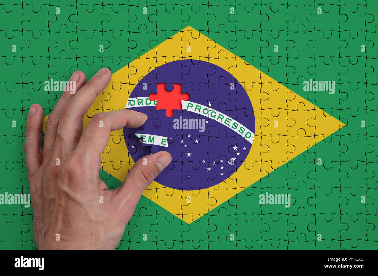 Brazil flag  is depicted on a puzzle, which the man's hand completes to fold. - Stock Image