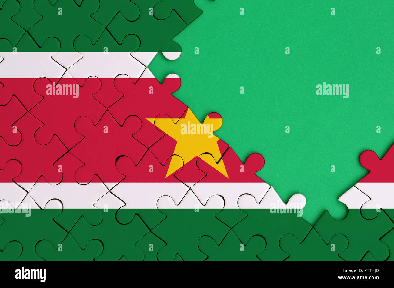 Suriname flag  is depicted on a completed jigsaw puzzle with free green copy space on the right side. - Stock Image