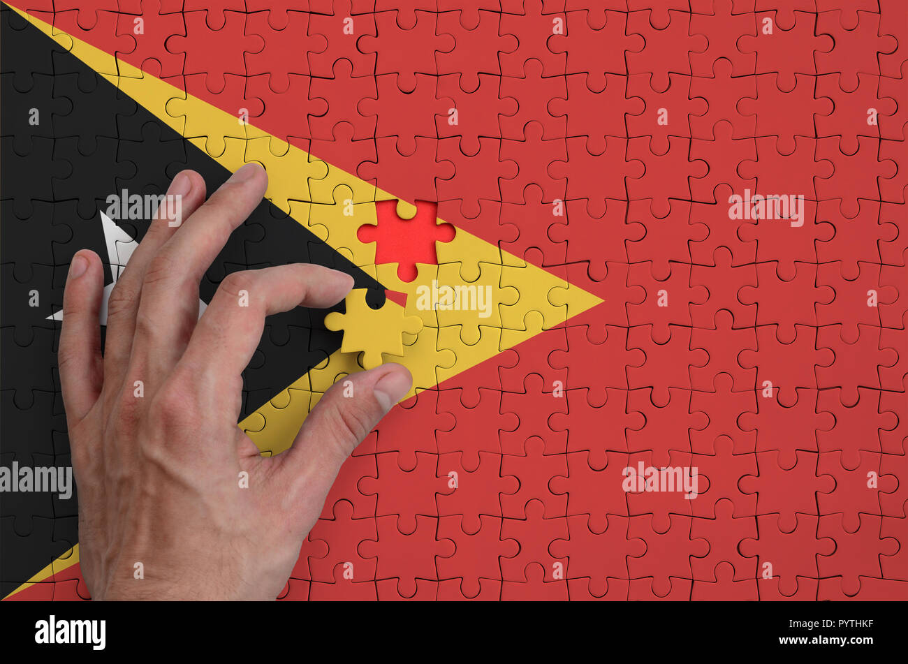 Timor Leste flag  is depicted on a puzzle, which the man's hand completes to fold. Stock Photo